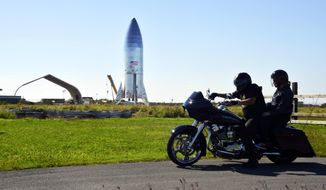 FILE - In this Jan. 12, 2019 file photo, a motorcyclist rides near the SpaceX prototype Starship hopper at the Boca Chica Beach site in Texas. SpaceX says it will build its Mars spaceship in south Texas instead of the Port of Los Angeles, dealing another blow to the local economy only days after the company announced massive layoffs. The Southern California-based company announced Wednesday, Jan. 16, 2019 that test versions of its Starship and Super Heavy rocket will be assembled at its Texas launch facility in a move to streamline operations. (Miguel Roberts/The Brownsville Herald via AP, File)