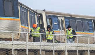Metropolitan Atlanta Rapid Transit Authority (MARTA) employees inspect an out-of-service train that got stuck on the tracks just north of Hartsfield-Jackson International Airport, Wednesday, Jan. 16, 2019, in Atlanta. Rail Operations Chief Dave Springstead says normal service to the airport may not resume until Thursday because officials need to bring in a crane to lift the train. (John Spink/Atlanta Journal-Constitution via AP)