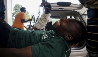 An injured man on a stretcher is loaded into a medical vehicle to be taken to hospital after being being beaten by soldiers in the Sizinda Township, Bulawayo, Zimbabwe Wednesday, Jan 16, 2019. Widespread reports of violence continued as Zimbabwe faced a third day of protests over what has become the world's most expensive gasoline. (AP Photo/KB Mpofu)