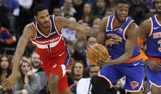 Washington Wizards forward Trevor Ariza (1), left go after the ball with New York Knicks guard Emmanuel Mudiay (1), during an NBA basketball game between New York Knicks and Washington Wizards at the O2 Arena, in London, Thursday, Jan.17, 2019. (AP Photo/Alastair Grant)