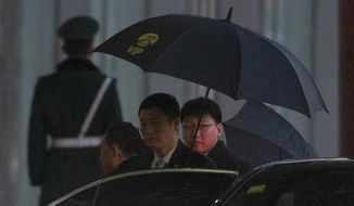 Kim Yong Chol, left, a North Korean senior ruling party official and former intelligence chief, is shielded with umbrellas as he arrives at the VIP terminal of the Beijing International airport in Beijing Thursday, Jan. 17, 2019. Kim arrived in Beijing on Thursday, reportedly en route to the United States for talks ahead of a possible second summit between President Donald Trump and North Korean leader Kim Jong Un. (AP Photo/Ng Han Guan)