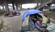 In this Feb. 9, 2016, file photo, a man lies in a tent with others camped nearby, under and near an overpass in Seattle. Microsoft pledged $500 million to address homelessness and develop affordable housing in response to the Seattle region's widening affordability gap. The company, which plans a news conference Thursday, Jan. 17, 2019, will split the funds three ways. (AP Photo/Elaine Thompson, File)