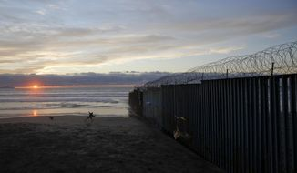 "FILE - In this Jan. 9, 2019, file photo, a man throws a ball for his dog next to the border wall topped with razor wire in Tijuana, Mexico. In his demands that Congress set aside $5.7 billion for a border wall, President Donald Trump insists a physical barrier would stop heroin entering the U.S. from Mexico. But U.S. statistics, analysts and testimony at the trial of drug kingpin Joaquin ""El Chapo"" Guzman in New York show that most hard drugs entering the U.S. from Mexico come through land ports of entry staffed by agents, not open sections of the border. (AP Photo/Gregory Bull, File)"