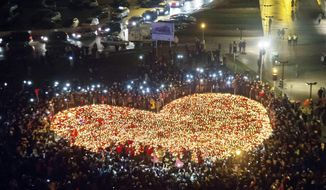 People stand by a heart shaped with candles as a tribute to slain President of Gdansk Pawel Adamowicz in Gdansk, Poland, Wednesday, Jan. 16, 2019. (AP Photo/Wojciech Strozyk)