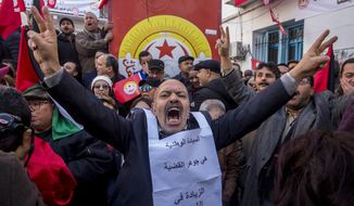Tunisian workers stage a protest in front of the national union headquarters in the capital Tunis, Thursday, Jan. 17, 2019. Workers around Tunisia are on strike to demand higher pay in a standoff with a government struggling to tame unemployment, poverty and social tensions. (AP Photo/Hassene Dridi)