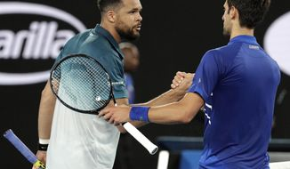 Serbia's Novak Djokovic, right, is congratulated by France's Jo-Wilfried Tsonga after winning their second round match at the Australian Open tennis championships in Melbourne, Australia, Friday, Jan. 18, 2019.(AP Photo/Aaron Favila)