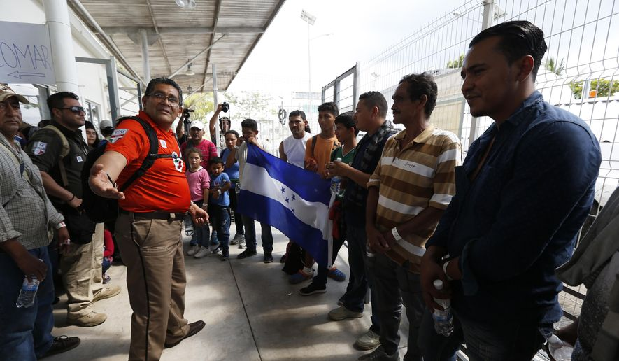 A Mexican immigration official welcomes a group of migrants as they cross the border into Mexico from Guatemala, near Ciudad Hidalgo, Chiapas State, Mexico, Thursday, Jan. 17, 2019. Hundreds of Central American migrants are walking and hitchhiking through the region as part of a new caravan of migrants hoping to reach the United States. (AP Photo/Marco Ugarte) ** FILE **