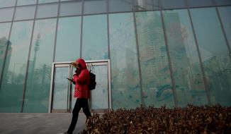 In this Jan. 12, 2019, photo, a man walks by a vacant retail space window panels at the Central Business District in Beijing. China's slowing economy is squeezing the urban workers and entrepreneurs the ruling Communist Party is counting on to help transform this country from a low-wage factory floor into a prosperous consumer market. (AP Photo/Andy Wong)