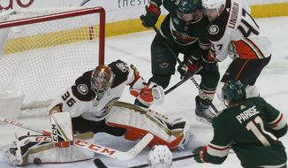 Anaheim Ducks goalie John Gibson, left, stops a shot as Hampus Lindholm, right, of Sweden, keeps Minnesota Wild's Eric Staal away from the rebound in the third period of an NHL hockey game, Thursday, Jan. 17, 2019, in St. Paul, Minn. The Ducks won 3-0. (AP Photo/Jim Mone)