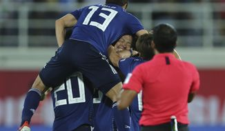 Japan players celebrate after Japan's Tsukasa Shiotani, centre, scored his side's second goal during the AFC Asian Cup group F soccer match between Japan and Uzbekistan at Khalifa bin Zayed Stadium in Al Ain, United Arab Emirates, Thursday, Jan. 17, 2019. (AP Photo/Kamran Jebreili)