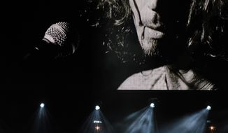 """Toni Cornell, daughter of the late singer Chris Cornell, performs with Ziggy Marley, bottom left, underneath a video image of her father during """"I Am The Highway: A Tribute to Chris Cornell"""" at The Forum, Wednesday, Jan. 16, 2019, in Inglewood, Calif. (Photo by Chris Pizzello/Invision/AP)"""