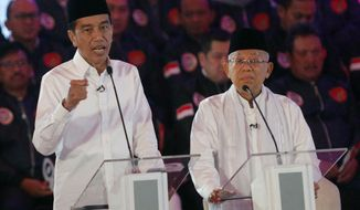 Indonesian President Joko Widodo, left, delivers a speech with running mate Ma'ruf Amin, right, during a televised debate in Jakarta, Indonesia, Thursday, Jan. 17, 2019.  Indonesia is gearing up to hold its presidential election on April 17 that will pit in the incumbent against the former general.(AP Photo / Tatan Syuflana)