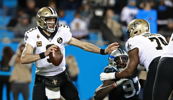 FILE - In this Dec. 17, 2018, file photo, New Orleans Saints' Drew Brees (9) scrambles away from a Carolina Panthers defender during the first half of an NFL football game in Charlotte, N.C. Offense wins championships in the new NFL. For the first time since the league expanded to 32 teams in 2002, none of the teams playing in the conference title game have a defense ranked in the top 10 in total yards. Only New England is among the top 10 in fewest points allowed. But, the Chiefs, Patriots, Saints and Rams do possess the four most prolific offenses in the league. (AP Photo/Jason E. Miczek, File) **FILE**