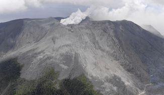 A smoke column rises from Shindake volcano after its eruption in Kuchinoerabu island, southern Japan, Thursday, Jan. 17, 2019. Japan Meteorological Agency said Thursday's eruption caused volcanic rocks flying out of the crater and pyroclastic flows pouring down but have not reached as far as the residential area 2 kilometers (1.2 mile) away. (Kyodo News via AP)