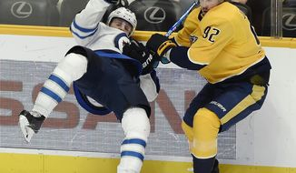 Nashville Predators center Ryan Johansen (92) checks Winnipeg Jets defenseman Sami Niku (83), of Finland, into the boards during the first period of an NHL hockey game Thursday, Jan. 17, 2019, in Nashville, Tenn. (AP Photo/Mark Zaleski)