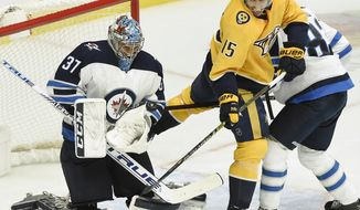 Winnipeg Jets goaltender Connor Hellebuyck (37) stops a shot as Nashville Predators right wing Craig Smith (15) looks for a rebound during the second period of an NHL hockey game Thursday, Jan. 17, 2019, in Nashville, Tenn. (AP Photo/Mark Zaleski)