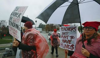 Teachers, parents and students picket under the rain in downtown Los Angeles Thursday, Jan. 17, 2019. A new round of contract negotiations began between Los Angeles school district officials and a teachers union as thousands of educators picketed in the rain. The announcement that the two sides were sitting down Thursday for the first time in nearly a week didn't indicate whether any new contract offers would be on the table. Union officials tempered expectations, saying a quick deal was unlikely. District officials have said teacher demands could bankrupt the school system. (AP Photo/Damian Dovarganes)