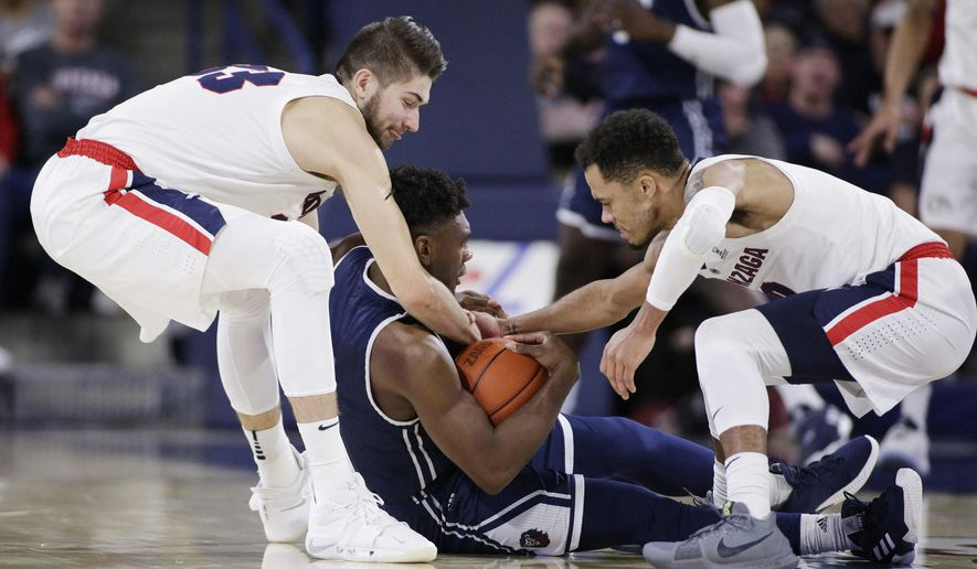 Gonzaga forward Killian Tillie, left, and guard Geno Crandall, right, tie up Loyola Marymount guard James Batemon during the first half of an NCAA college basketball game in Spokane, Wash., Thursday, Jan. 17, 2019. (AP Photo/Young Kwak)