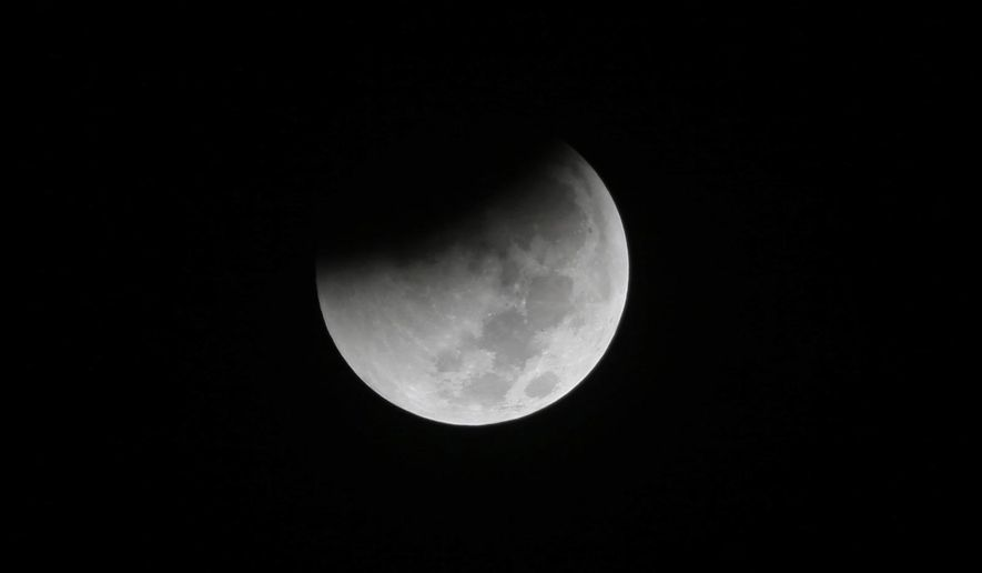In this Saturday, Aug. 28, 2018, file photo, Earth starts to cast its shadow on the moon during a complete lunar eclipse seen from Jakarta, Indonesia. Starting Sunday evening, Jan. 20, 2019, all of North and South America will be able to see the only total lunar eclipse of 2019 from start to finish this weekend. (AP Photo/Tatan Syuflana)