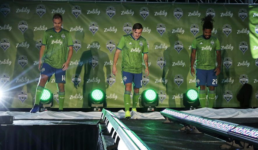 Seattle Sounders' Chad Marshall, left, Jordan Morris, center, and Roman Torres, right, model new MLS soccer jerseys, Thursday, Jan. 17, 2019, during an event to unveil the Sounders' new jersey sponsorship with Zulily, a Seattle-based online clothing retailer. Zulily also announced a jersey sponsorship with the Seattle Reign in the National Women's Soccer League. (AP Photo/Ted S. Warren)