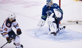 Edmonton Oilers right wing Alex Chiasson (39) scores past Vancouver Canucks goaltender Jacob Markstrom (25) during the shootout in an NHL hockey game Wednesday, Jan. 16, 2019, in Vancouver, British Columbia. (Jonathan Hayward/The Canadian Press via AP)