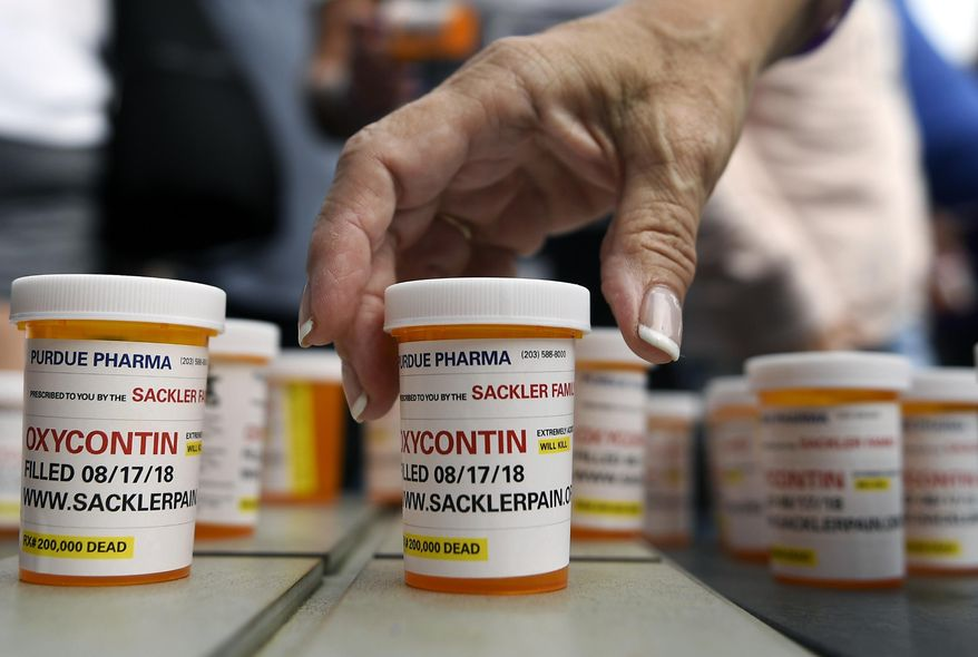 Family and friends who have lost loved ones to OxyContin and opioid overdoses leave pill bottles in protest outside the headquarters of Purdue Pharma, which is owned by the Sackler family, in Stamford, Conn. (AP Photo/Jessica Hill) ** FILE **