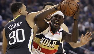 New Orleans Pelicans' Jrue Holiday, right, looks to shoot against Golden State Warriors' Stephen Curry (30) during the first half of an NBA basketball game Wednesday, Jan. 16, 2019, in Oakland, Calif. (AP Photo/Ben Margot)