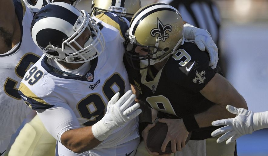 FILE - In this Nov. 26, 2017, file photo, New Orleans Saints quarterback Drew Brees, right, gets sacked by Los Angeles Rams defensive end Aaron Donald during the first half of an NFL football game, in Los Angeles. The Rams, with unanimous All-Pro defensive tackle Aaron Donald take on the Saints in the NFC Championship on Sunday, Jan. 20, 2019.(AP Photo/Mark J. Terrill, File)