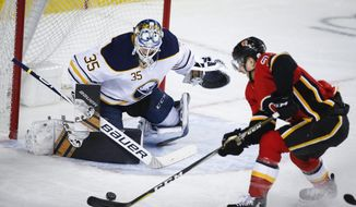 Buffalo Sabres goalie Linus Ullmark, left, of Sweden, guards the net as Calgary Flames' Garnet Hathaway tries to score on a breakaway during the first period of an NHL hockey game, Wednesday, Jan. 16, 2019, in Calgary, Alberta. (Jeff McIntosh/The Canadian Press via AP)