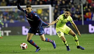 Levante defender Borja Mayora, left, duels for the ball with Barcelona's Chumi during the la Copa del Rey round of 16 first leg soccer match between Levante and Barcelona at the Ciutat de Valencia stadium in Valencia, Spain, Thursday Jan. 10, 2019. (AP Photo/Alberto Saiz)