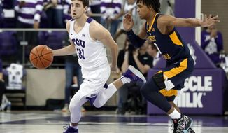 """In this Jan. 15, 2019, photo, TCU guard Owen Aschieris (31) moves the ball up court as West Virginia's Trey Doomes (0) defends during an NCAA college basketball game in Fort Worth, Texas. TCU walk-on player Aschieris was sitting in a team meeting when a university police officer walked in and asked to speak to him. """"I was racking my brain to think about what I might have done wrong in the past of my entire life,"""" Aschieris said. """"It was crazy."""" (AP Photo/Tony Gutierrez)"""
