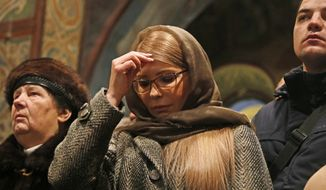 Ukrainian opposition leader Yulia Tymoshenko, center, crosses herself during the service marking Orthodox Christmas and celebrating independence of Ukrainian Orthodox Church in the St. Sophia Cathedral in Kiev, Ukraine, Monday, Jan. 7, 2019. (AP Photo/Efrem Lukatsky)