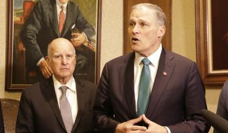 Washington Gov. Jay Inslee, left, speaks to the media as former California Gov. Jerry Brown looks on, in Olympia, Wash., Thursday, Jan. 17, 2019. Inslee, Brown and several Washington lawmakers met to discuss Inslee's climate agenda. (AP Photo/Rachel La Corte)