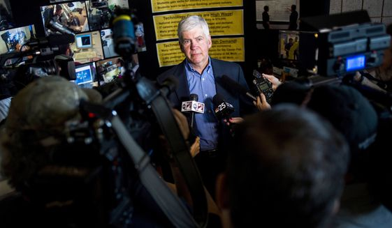 In this Monday, June 6, 2016, file photo, journalists surround around Gov. Rick Snyder to ask him questions about the Flint water crisis after he toured skilled trades programs at Mott Community College in Flint, Mich. Flint had one of the worst man-made environmental debacles in U.S. history. Lead infected the distribution system in the city of 100,000, which was under the thumb of financial managers appointed by Snyder. Officials finally took action after a doctor reported high levels of lead in children. (Jake May/The Flint Journal - MLive.com via AP)