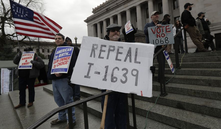 """Rick Howell, of Wenatchee, Wash., holds a sign that reads """"Repeal I-1639"""" as he takes part in a gun-rights rally, Friday, Jan. 18, 2019, at the Capitol in Olympia, Wash. Initiative 1639, which was passed by voters in November, 2018, is a package of gun regulations that includes raising the legal age to buy any semi-automatic rifle to 21. (AP Photo/Ted S. Warren)"""