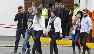 Family members of victims of a bombing cry outside the entrance to the General Santander police academy where the bombing took place in Bogota, Colombia, Thursday, Jan. 17, 2019. (AP Photo/John Wilson Vizcaino)