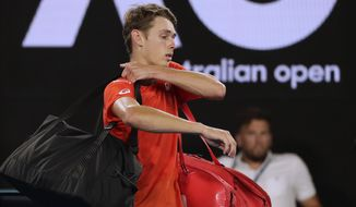 Australia's Alex de Minaur leaves Rod Laver Arena after losing his third round match against Spain's Rafael Nadal at the Australian Open tennis championships in Melbourne, Australia, Friday, Jan. 18, 2019. (AP Photo/Kin Cheung)