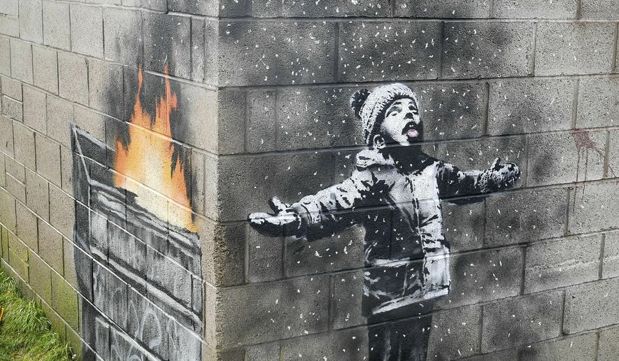 "FILE -  In this file photo dated Dec, 20, 2018, showing an artwork by Banksy on the side of a garage depicts a child dressed for snow playing in the falling ash and smoke from a skip fire, in Port Talbot, Wales.  The artwork has been sold to an Essex art dealer for a ""six-figure sum"", although the mural will stay in its current location for about two-years, it is revealed Friday Jan. 18, 2019. (Ben Birchall/PA FILE via AP)"