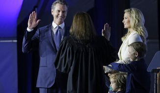 FILE - In this Jan. 7, 2019, file photo California Gov. Gavin Newsom takes the Oath of Office from state Supreme Court Chief Justice Tani Gorre Cantil-Sakauye during his inauguration in Sacramento, Calif. California's new governor won't be living in the historic governor's mansion after all.  The Sacramento Bee reported Friday, Jan. 18, 2019, that the family plans to move to a $3.7 million, six-bedroom house in a Sacramento suburb. The newspaper cited property records showing the family bought the Fair Oaks home in December.  (AP Photo/Rich Pedroncelli, File)