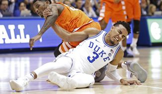 Duke's Tre Jones (3) tangles with Syracuse's Frank Howard during the first half of an NCAA college basketball game in Durham, N.C., Monday, Jan. 14, 2019. Jones was injured on the play and left the court. No. 1-for-now Duke will have to figure out how to play without perhaps its most irreplaceable player now that point guard Tre Jones is out indefinitely with a shoulder injury. (AP Photo/Gerry Broome)