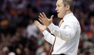 "FILE - In this March 15, 2018, file photo, Florida head coach Mike White gestures during the first half of a first-round game against St. Bonaventure at the NCAA college basketball tournament in Dallas. Florida coach Mike White says he has a team of ""clock-watchers,"" guys seemingly content to coast through the final minutes of games and hope to win. It's the only way he can explain how the Gators have struggled down the stretch in Southeastern Conference play. (AP Photo/Brandon Wade, File)"