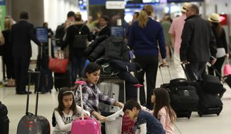 Travelers organize their luggage before entering a security checkpoint at Miami International Airport, Friday, Jan. 18, 2019, in Miami. (AP Photo/Lynne Sladky) ** FILE **