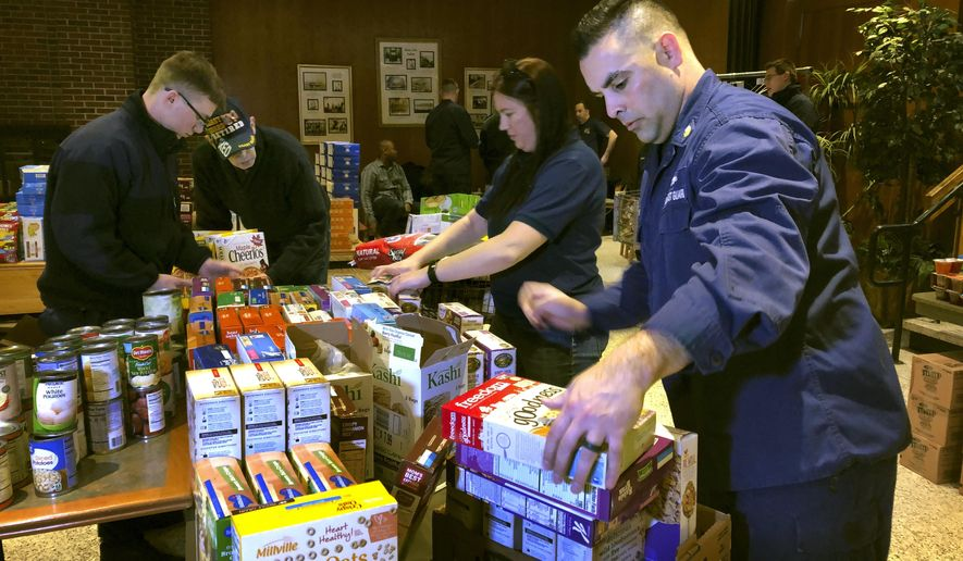 In this Thursday, Jan. 17, 2019, photo, U.S. Coast Guard Culinary Specialist Jerry Wright, right, and Petty Officer 2nd Class Lauren Laughlin, second from right, stack boxes of donated cereal at a pop-up food pantry created at the Coast Guard Academy in New London, Conn. The pantry was created by local Coast Guard-related advocacy groups to help hundreds of civilian and non-civilian Coast Guard employees to help makes ends meet during the partial federal government shutdown. (AP Photo/Susan Haigh)