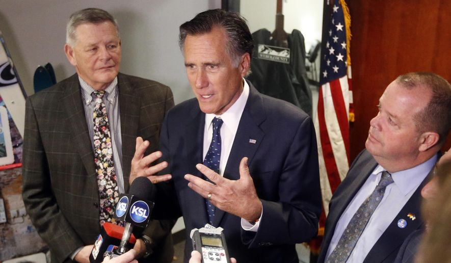 U.S. Sen. Mitt Romney, center, R-Utah, speaks with reporters after visiting with local officials to discuss how the four-week partial government shutdown is impacting an area with several major federal employers, including the Internal Revenue Service, Friday Jan., 18, 2019, in Ogden, Utah. (AP Photo/Rick Bowmer)