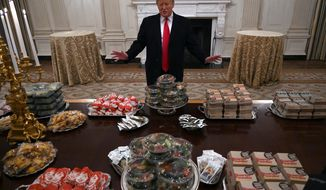 In this Jan. 14, 2019 photo, President Donald Trump talks to the media about the table full of fast food in the State Dining Room of the White House in Washington, for the reception for the Clemson Tigers. The partial government shutdown is hitting home for President Trump in a very personal way. He lives in government-run housing, after all. Just 21 of the roughly 80 people who help care for the White House _ from butlers to electricians to chefs _ are reporting to work. The rest have been furloughed. (AP Photo/Susan Walsh)
