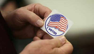 In this May 8, 2018, file photo, a person holds a sticker after placing his vote at the Durham County Library North Regional in Durham, N.C. (AP Photo/Gerry Broome, file)