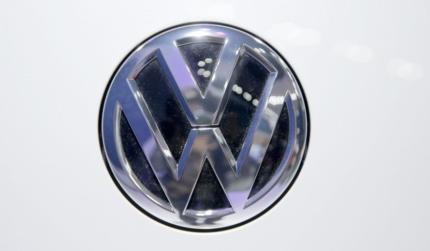 In this Wednesday, Feb. 3, 2016, photo, Volkswagen logo is seen on a vehicle displayed at the Auto Expo in Greater Noida, near New Delhi, India. The Volkswagen Group says that it will deposit a fine of 1 billion rupees ($14.2 million) imposed by India's green panel for installing software that allegedly cheated pollution testing devices. (AP Photo/Tsering Topgyal)