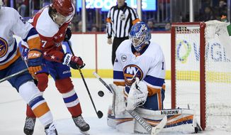 New York Islanders goaltender Thomas Greiss (1) stops the puck next to Washington Capitals right wing T.J. Oshie (77) during the second period of an NHL hockey game Friday, Jan. 18, 2019, in Washington. (AP Photo/Nick Wass) ** FILE **