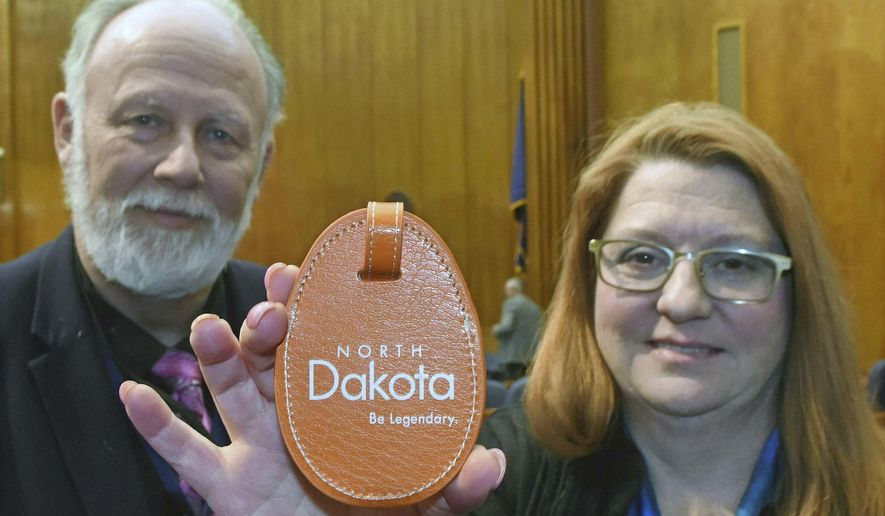 In this Thursday. Jan. 17, 2019 photo, state Reps. Marvin Nelson, D-Rolla,, left, and LaurieBeth Hager, D-Fargo, hold a tag with the official North Dakota logo in Bismarck, N.D. The two lawmakers are not fans of the state's official logo. (Tom Stromme/The Bismarck Tribune via AP)