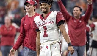 In this Dec. 1, 2018, photo, Oklahoma quarterback Kyler Murray (1) celebrates on the sidelines after throwing a touchdown against Oklahoma during the second half of the Big 12 Conference championship NCAA college football game, in Arlington, Texas. A record number of college football players are bypassing remaining years of eligibility to enter the NFL draft, including Heisman Trophy winner Kyler Murray. (AP Photo/Jeffrey McWhorter) **FILE**